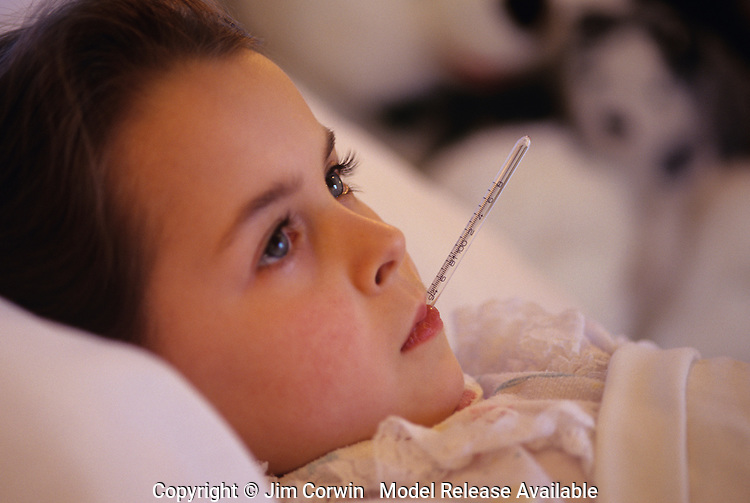 Young girl ( 7 years old) in bed with flu/cold getting her temperature taken by her mother with thermomter in her mouth.  MR
