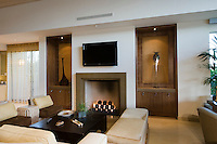 Beautiful modern living room featuring contemporary furniture and a lit fireplace.