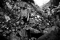 A young teenaged miner carries heavy solid coal rocks on her head while walking barefoot for kilometers, across sharp stones and hot coals in the open-pit coalmines of Dhanbad, Jharkhand, India. She, like many other girls, has been working since childhood in the mines and has never been to school. Photo by Suzanne Lee