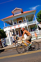 Cycling in front of historic Wo Hing Temple, Front Street, Lahaina, Maui