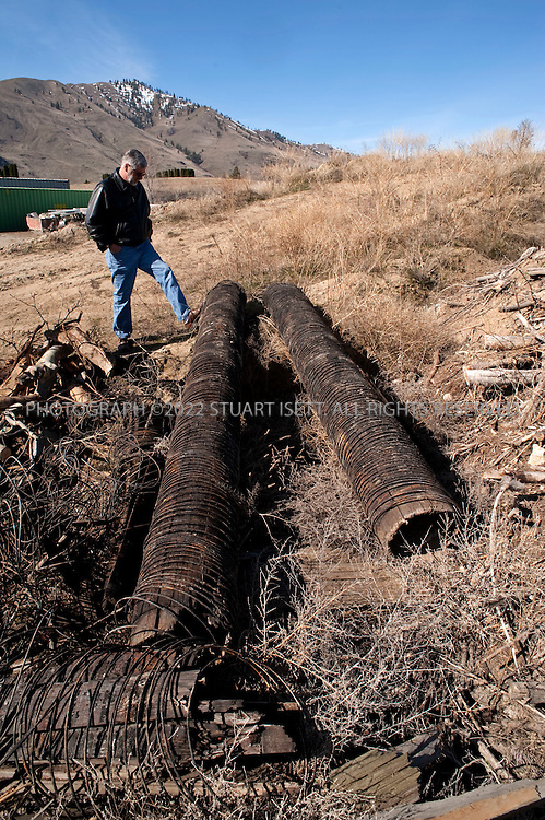 4/6/2009--Chelan, WA, USA.Dwane Van Epps, the public works administrator for Chelan, WASH, inspects old wood water pipes that have been replaced. Part of Chelan's, water infrastructure still includes these old wood water pipes used to deliver water to homes in the town...©2009 Stuart Isett. All rights reserved.