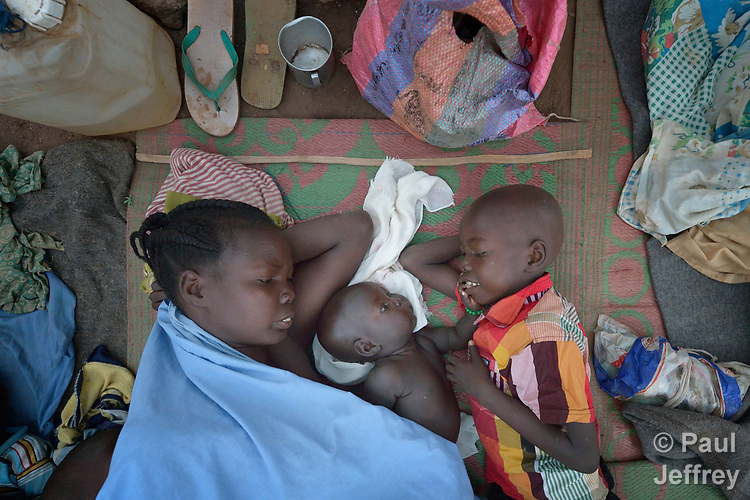 A mother and two of her children wake up after sleeping in the open in a camp for over 5,000 internally displaced persons in an Episcopal Church compound in Wau, South Sudan. Most of the families here were displaced by violence early in 2017, after a larger number took refuge in other church sites when widespread armed conflict engulfed Wau in June 2016.<br /> <br /> Norwegian Church Aid, a member of the ACT Alliance, has provided relief supplies to the displaced in Wau, and has supported the South Sudan Council of Churches as it has struggled to mediate the conflict in Wau.