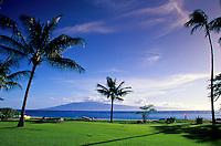 Tourists walking along Kaanapali beach with view of Island of Lanai, West coast Maui
