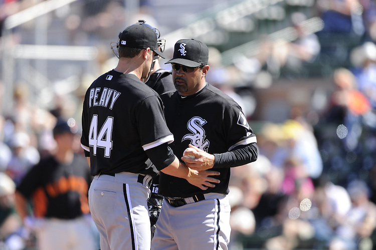 SCOTTSDALE, AZ - MARCH 09:  Manager Ozzie Guillen #13 takes the ball from Jake Peavy #44 of the Chicago White Sox during a pitching change against the San Francisco Giants on March 09, 2011 at Scottsdale Stadium in Scottsdale, Arizona. The Giants defeated the White Sox 4-2.  (Photo by Ron Vesely)