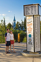 Tourists from Belgium enjoy the welcome to Fairbanks milepost sign and other sights in downtown Fairbanks on a sunny summer evening.