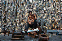 "Indonesia - Bangka Island - Rebo - Muin Dain, 53, from Sulawesi Island is sitting in front of his house on top of some rusted mining tools. He arrived in Bangka from Sulawesi when he was 2, together with his parents. He has mined onshore, watering the soil for six year, from 2000 to 2006. Today, he lives in Rebo, where one of his sons works on a pontoon. ""I buried many of my friends dying because of tin mining"" he remembers."