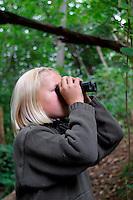 Mädchen, Kind beobachtet Vögel im Wald mit dem Fernglas