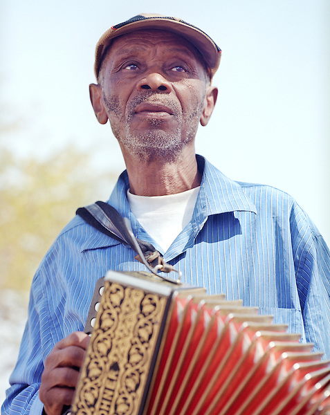 "Grigorio Viaz nicknamed ""Code de Dona"" ( Grandmothers's favorite) sits outside his home in Sao Francisco playing his accordion.  Music and dance are a focal point of Cape Verdean culture. The most popular traditional music and dance type is morna. Lyrics are usually in Cape Verdean Creole, and instrumentation often includes cavaquinho, clarinet, accordion, violin, piano and guitar. Morna is considered the national music of Cape Verde."