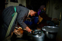 Ladakhi women cook dinner on 1st June 2009, in the 200 year old kitchen for friends, family and guests of a home stay programme with a traditional Ladakhi family in Ulley Valley, a scattered village of only 5 houses, one school, 38 people, 4 school children, and 4 pet dogs. The village is not accessible by road. The home stay program is managed by 'Snow Leopard Conservation Organisation', an NGO that helps families in the mountains that face constant snow leopard attacks on their live stock. Ulley is located in the region of Ladakh, located in the Indian Himalayas, in the northern state of Jammu and Kashmir. Photo by Suzanne Lee