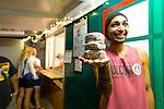 A local man buys freshly made Poi Doughnuts. Hot bread served at night at Kanemitsu Bakery in Kaunakakai, Molokai, Hawaii, USA