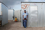 "CAPE TOWN, SOUTH AFRICA - MAY 3: Deborah Schericka, age 32, stands outside her tin shack with her son Frazier Sherick, age 10, on May 3, 2010, in Blikkiesdorp about 40 kilometers south of Cape Town, South Africa. Deborah used to live on the streets of Central Cape Town and she was recently forced to move away and dumped at this site. She had lived for years on the streets of Cape Town. The street people who refused to move here were put in prisons, such as Pollsmoor. Blikkiesdorp, which is Afrikaans for ""Tin Can Town"", was given its name by its residents because of the row-upon-row of tin-like shacks made of corrugated iron. It was built by the City of Cape Town in 1997 and about 1600 one-roomed shacks were built. It has been known for its bad conditions and a dumping ground for shack dwellers from other areas around Cape Town. Recently many street people in Cape Town has been forcefully removed and relocated to this place. The ones that have refused has been put in holdings cells or prisons such as Pollsmoor Prison. This campaign has  identified in the preparation for the soccer World Cup, who starts on June 11, 2010 and goes on for a month. The City of Cape Town doesn't want international visitors to be hassled by street people. (Photo by Per-Anders Pettersson)"