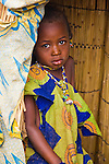"""A young Fulani girl stands just inside the door of her mud hut in the small village of Bele Kwara in southwestern Niger.  While not as elaborate as many facial scars, she sports the two near-vertical lines on either side of her nose, which are traditional facial scars of the Fulani tribe.  In the background stands a mat made from stalks of millet weaved together with strips of leather. The mat is called """"yombeeo"""" in fulfulde, the language of the Fulani people, and comes from """"yombe,"""" the word for """"millet stalks."""""""