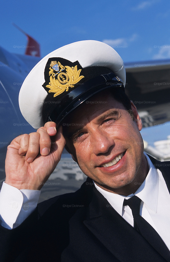 """John Travolta, touching his hat in salute. Captain and pilot, of his own jumbo jet...John Travolta is pilot of his very own jumbo jet, a 1964 Boeing 707-100 series. In 2003, John Travolta flew his jumbo jet around the world, in partnership with Quantas, to rekindle confidence in commercial aviation, and to remind us that elegance and style are a part of flying. The crew are dressed in tailor made authentic uniforms from the Quantas museum. The men's uniforms are styled on British Naval uniforms and the ladies' designed by Chanel. His jumbo jet sports a personalised number plate N707JT which speaks for itself. The aircraft is named """"Jett Clipper Ella"""" dedicated to his son and daughter. This jumbo together with his other aircraft are housed in purpose built hangars at his home in Florida, USA."""