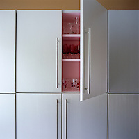 The open door to this kitchen cupboard reveals its pink-painted interior