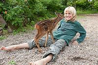 Rehkitz, Reh-Kitz, verwaistes, pflegebedürftiges Jungtier wird in menschlicher Obhut großgezogen, Kind, Junge spielt mit Kitz im Garten, Tierkind, Tierbaby, Tierbabies, Europäisches Reh, Ricke, Weibchen, Capreolus capreolus, Roe Deer, Chevreuil