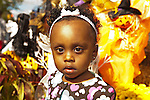 African-American toddler girl closeup by autumn decorations, soft focus orange and brown Halloween and Thanksgiving holidays, at fall Merrick Street Fair, October 22, 2011, editorial