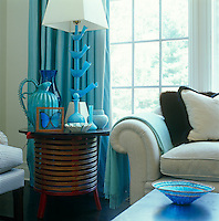 Great confidence is required to work with turquoise but it is stunningly pulled off in this living room where the focus is the amazing collection of Murano glass on an antique side table