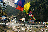 A mule train hauls supplies over the Larja Bridge on the trail to Namche Bazaar. The narrow metal bridge spans the Dudh Kosi river and is strung with scores of Buddhist prayer flags.