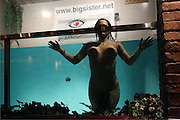 Prague, Czech Republic - April, 2007. A naked prostitute enjoying a bath in aquarium-like swimming pool in the bar area of the Big Sister brothel. The swimming pool is open to the bar / restaurant, so that men mingeling with prostitutes can enjoy the view of  the  naked women as well as their fellow clients, splashing around.  The advertising for the Big Sister website is placed at most places, visible on the cameras.