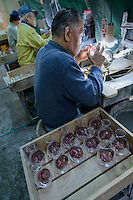 Artisans work on sake flashes decorated using Edokiriko technique. Shimizu Glass, Tokyo, Japan, January 14, 2015. Edokiriko is a style of cut glass that dates back to 1834 and is similar to British cut glass. It makes use coloured glass and highly-intricate Japanese motifs.