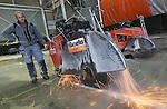 Foto: VidiPhoto<br /> <br /> NIJMEGEN - Met een gezamenlijk vermogen van 350 pk ploegen vijf zware vloerzagen van Husqvarna dwars door de toplaag van een 60 cm dikke, zwaargewapende betonvloer van Royal Smit Transformers in Nijmegen. Door slijtage voldoet de ondergrond van de testhal nu niet meer en wordt deze razendsnel vernieuwd om luchtkussentransport van de megazware transformatoren weer mogelijk te maken. Vanwege de dikte van het beton en de zware wapening koos betonzaagbedrijf WIHA BV uit Dinxperlo voor de op dit moment meest geavanceerde diamantzaagmachines met emissiearme dieselmotoren. In maximaal 12 uur tijd dient 800 meter betonvloer op een diepte van 20 cm doorgezaagd te worden. Na het afvoeren van het puin krijgt de vloer een nieuwe bovenlaag van 20 cm dikte.  Op 5 januari 2015 is de testhal voor transformatoren weer gereed voor gebruik. Het is voor zover bekend voor het eerst dat vijf zware vloerzagen tegelijk worden ingezet.