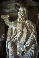 "Early Anglo Saxon sulpture of the an Apostle holding a manuscripot now part of the south porch of Malmesbury Abbey, Wiltshire, England. The apostles, apart from Peter who holds a crude key, have no distinguishing feature to allow identification. Some are holding books, none have halos and some hold their heads at awkward angles. These three styles are typical of Anglo Saxon art. The two panels are 10 ft long and 4ft 6"" high are date from the original Ango Saxon church of 705. They were probablbly built into the proch during the Norman rebuilding. The style of these sculptures is of the Roman Byzantine style and were probably sculpted by masions from Gaul.  Malmesbury Abbey, Wiltshire, England"