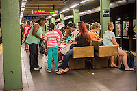 Travelers wait for their trains in the Times Square station in the New York subway on Saturday, September 27, 2014. (© Richard B. Levine)