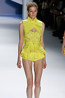 Marique Schimmel walks runway in a Yellow perforated super pique zipper corset with mackintosh cotton cross cross collar cutaway overlay and double layer drawstring peplum belt, and Yellow mackintosh cotton peplum boy shorts with cutout pocket detail, by Vera Wang, for the Vera Wang Spring 2012 collection, during Mercedes-Benz Fashion Week Spring 2012.