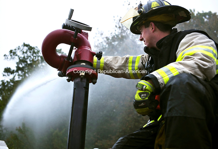Wolcott, CT- 03 October 2015-100315CM06-  Wolcott volunteer firefighter Bruce Cyr mans a deck water gun at the Wolcott Elementary School on Saturday.  Departments from Wolcott, Bristol, Southington and Prospect participated in the training exercise.     Christopher Massa Republican-American
