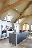 Packed with masses of storage, the bespoke kitchen cabinet also houses columns of hi-tech ovens