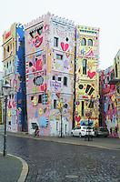 Described as &quot;the happiest house on earth,&quot; the Happy Rizzi House (Rizzihaus) in Brunswick is a day-glo masterpiece of cartoon-inspired architecture set smack in the heart of a staid German historic neighborhood.<br /> Standing in stark contrast to its old world surroundings, the Happy Rizzi House is the vision of New York pop artist James Rizzi (perhaps best known for designing the cover for Tom Tom Club's 1981 debut album) and architect Konrad Kloster. Representative of Rizzi's style, the structures are decorated in wild shapes and faces colored in bright pinks, yellows, and greens reminiscent of an 80's music video. Happy Rizzi House in Braunschweig. Das Happy Rizzi House (Eigenschreibweise Happy RIZZI House; meist nur &bdquo;Rizzi-Haus&ldquo; genannt) ist ein zeitgen&ouml;ssisches Geb&auml;ude in Braunschweig, das von dem US-amerikanischen K&uuml;nstler James Rizzi (1950&ndash;2011) entworfen und vom Braunschweiger Architekten Konrad Kloster umgesetzt wurde. Es befindet sich am Ackerhof.<br /> <br /> Es entstand auf Initiative eines Braunschweiger Galeristen. Die Idee zum Rizzi-Haus entstand 1997. Der Grundstein wurde w&auml;hrend des 26. Magnifestes, das vom 3. bis 5. September 1999 stattfand, durch den damaligen nieders&auml;chsischen Ministerpr&auml;sidenten Gerhard Glogowski gelegt. Nach zweij&auml;hriger Bauzeit war das aus neun verbundenen Teilbauk&ouml;rpern bestehende Haus fertiggestellt.