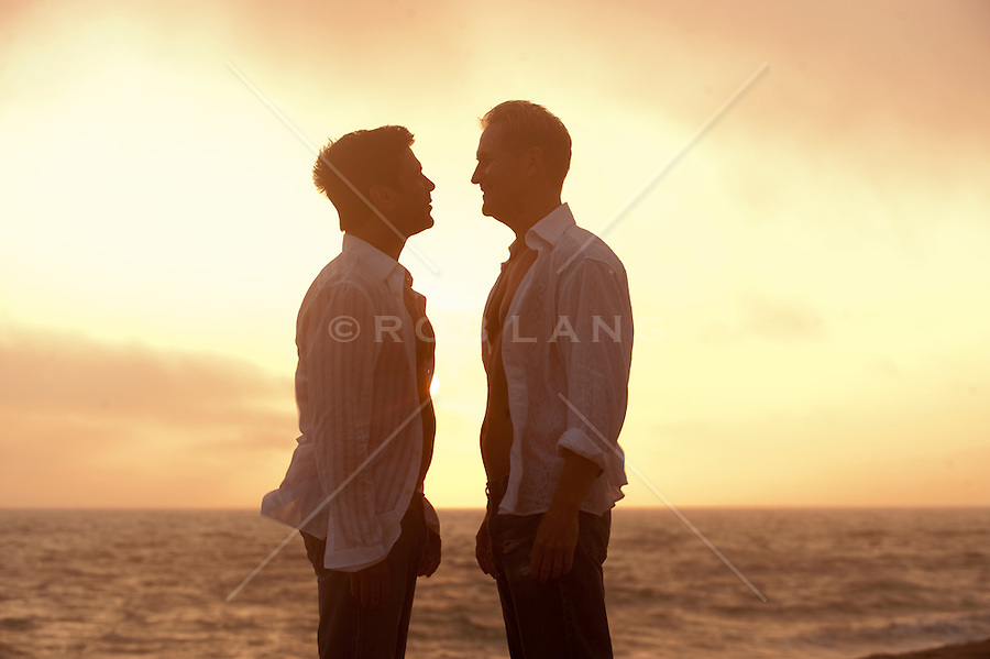 Two men getting ready to kiss on the beach