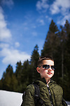 An 8 year old boy wears a pair of Maui Jim sunglasses that are too big for him while hiking in Bonner County, Idaho.