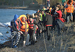 Refugees walk along the shoreline after they  landed on a beach near Molyvos, on the Greek island of Lesbos, on October 30, 2015, after crossing the Aegean Sea from Turkey. Local and international volunteers welcomed the arriving refugees with food and medical care and dry clothes before the newcomers proceeded on their way toward western Europe. Their boat to Greece was provided by Turkish traffickers to whom the refugees paid huge sums.