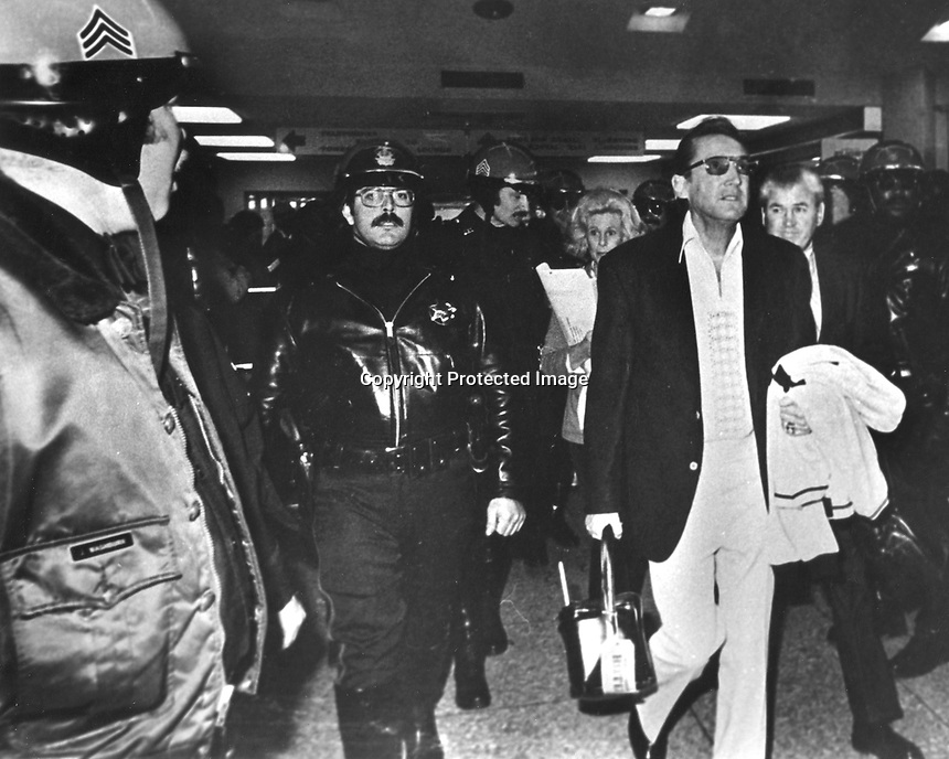 Oakland Raider general manager and owner Al Davis is escorted from the Oakland International Airport by Oakland Police after returning to Oakland from Los Angeles in 1995. (1995 photo by Ron Riesterer)