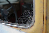 An old  yellow truck with cobwebs on the window.