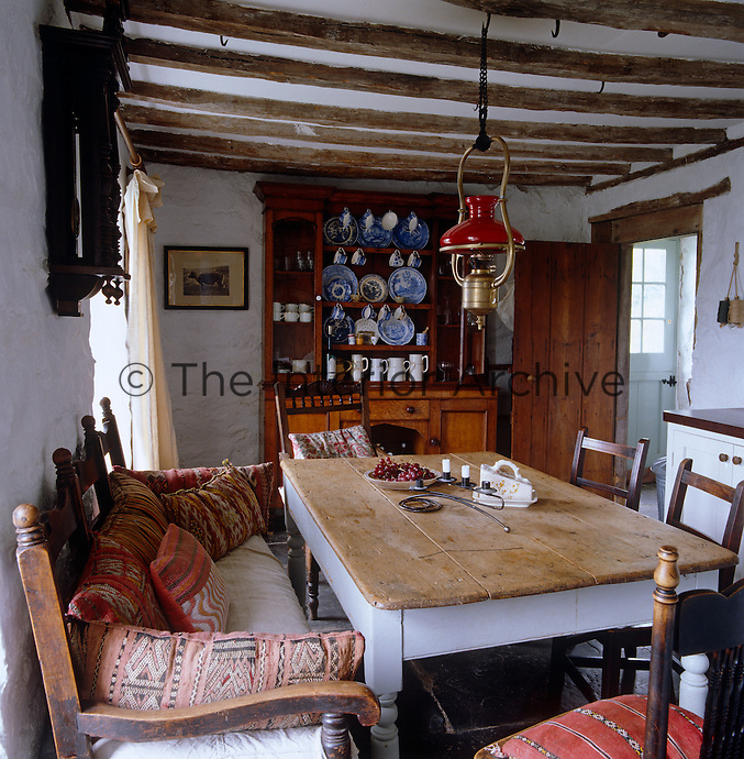The kitchen/dining room is furnished with a Welsh dresser, large kitchen table and wooden sofa covered in cushions