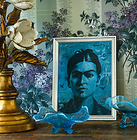 A small blue portrait of Frieda Kahlo sits amongst a collection of blue coloured glass