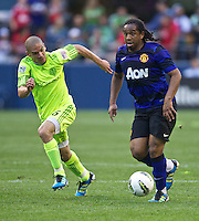 Manchester United midfielder Anderson, right looks to pass as Seattle Sounders FC midfielder Osvaldo Alonso pursues during play at CenturyLink Field in Seattle Wednesday July 20, 2011. Manchester United won the match 7-0.