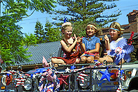 Three girls enjoy the annual Fourth of July Makawao Rodeo Parade in the upcountry town of Makawao. Maui's cowboy or paniolo town got its start in the early 1800s as a support community for the upcountry cattle ranches. Today you can still see the old hitching posts.