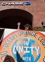 "A man wearing sunglasses holds the colorful ""Occupy Orange County in Unity with Occupy Wall Street"" sign in front of a Chase bank in Irvine, CA during the Saturday November 5 Occupy Orange County, Irvine march."