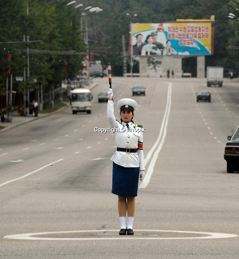 A traffic police-woman directs the very little traffic that exists on the streets of  PyongYang, the North Korean Capital.