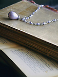 An old violet pearl necklace laid on old printed books, with a printed page at the bottom.