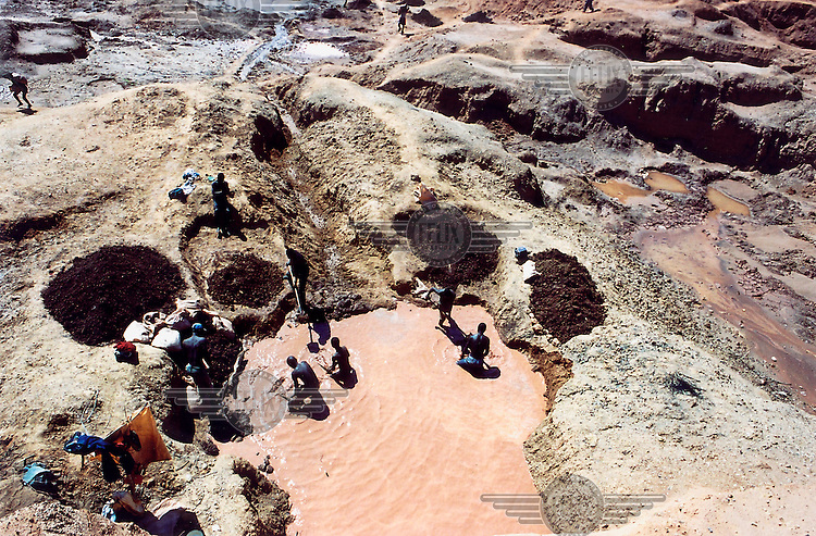 A government-held enclave in rebel-controlled territory. Diamond mining in a huge hand-dug pit. Digging and washing.