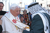Pope Benedict XVI, center left, receives a scarf as a present from a Palestinian man as Palestinian Prime Minister Salam Fayyad, second right, stand nearby during a ceremony at the Aida Refugee Camp, back dropped by the separation barrier in the West Bank town of Bethlehem, Wednesday, May 13, 2009.