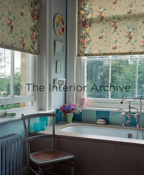The bathroom is lit by two adjacent sash windows with matching chintz blinds