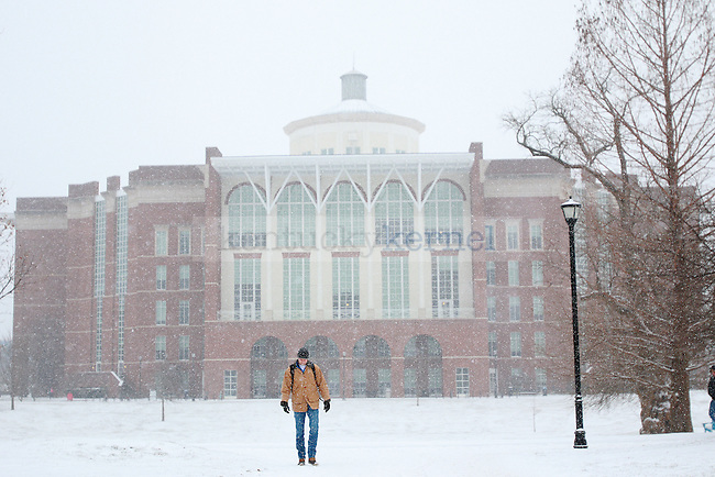 A student walks through the snow past the William T. Young Library after the first snowfall on campus at the University of Kentucky on Wednesday January, 20, 2015 in Lexington, Ky. Photo by Michael Reaves | Staff.