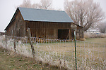 Washington, Chewelah. A rustic weathered barn and frost covered fence on a cold autumn morning.