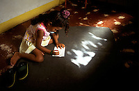 Aline da Silva, one of seven daughters of Absolón and Somália da Silva, draws on the floor of the family's living room. Paper, pens and even furniture are scarce. The family has difficulty affording the small fees and supplies needed to send their daughters to school.