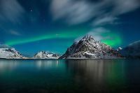 Northern lights shine in sky over Olstind mountain peak Moskenesøy, Lofoten Islands, Norway